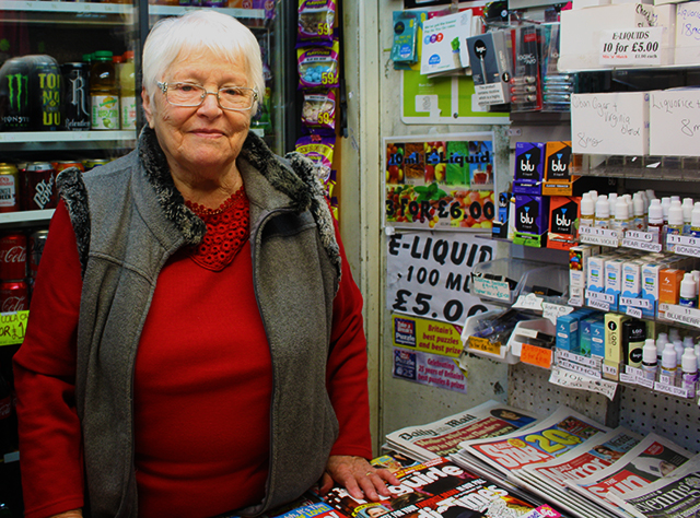 An elderly female shopkeeper from Leeds. Behind her is canned drinks. On the bench infront of her is covered in magazines and newspapers. She is pictured from the waist up and smiling at the camera.