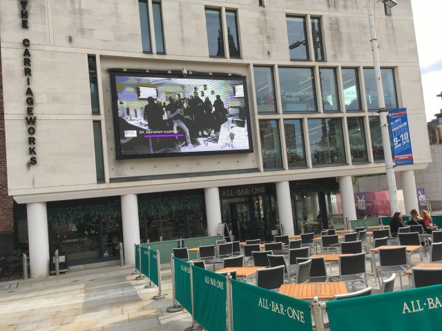 Chian's newsdays video plays in Millennium Square to an audience of thousands