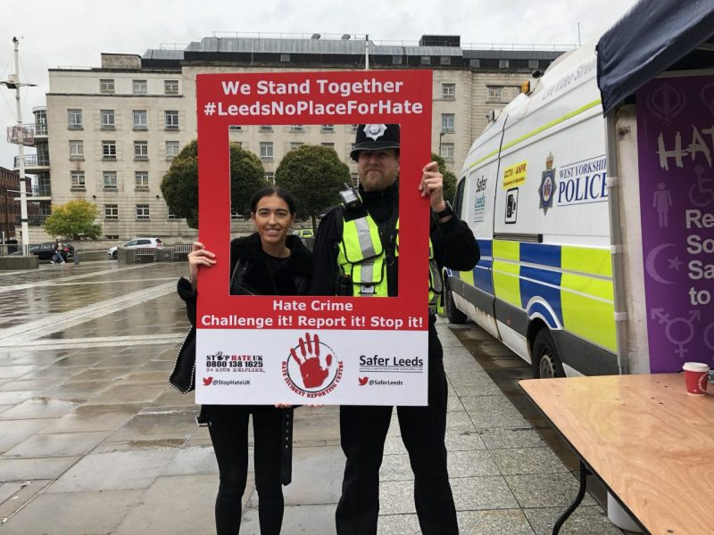 Ria Taylor stood with policeman holding up sign for Hate Crime Awareness Week.