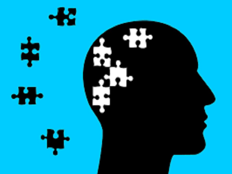 a black person's head with jigsaw puzzles in and around his head with a blue background